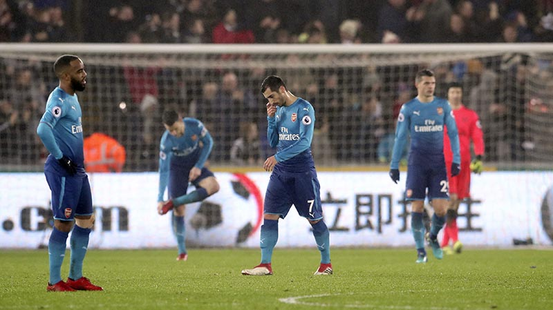 Arsenal's Henrikh Mkhitaryan (centre), looks dejected after Arsenal concede their third goal of the game during the English Premier League soccer match between Swansea City and Arsenal at the Liberty Stadium, Swansea, Wales, on Tuesday, January 30, 2018. Photo: Nick Potts/PA via AP