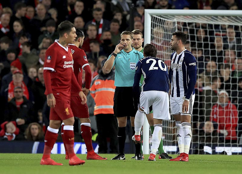 Match referee Craig Pawson (centre), disallows a third goal by West Bromwich Albion's Craig Dawson after a discussion with the Video Assistant Referee during the English FA Cup, fourth round soccer match between Liverpool and West Bromwich Albion, at the Anfield stadium, Liverpool, England, on Saturday January 27, 2018. Photo: Peter Byrne/PA via AP