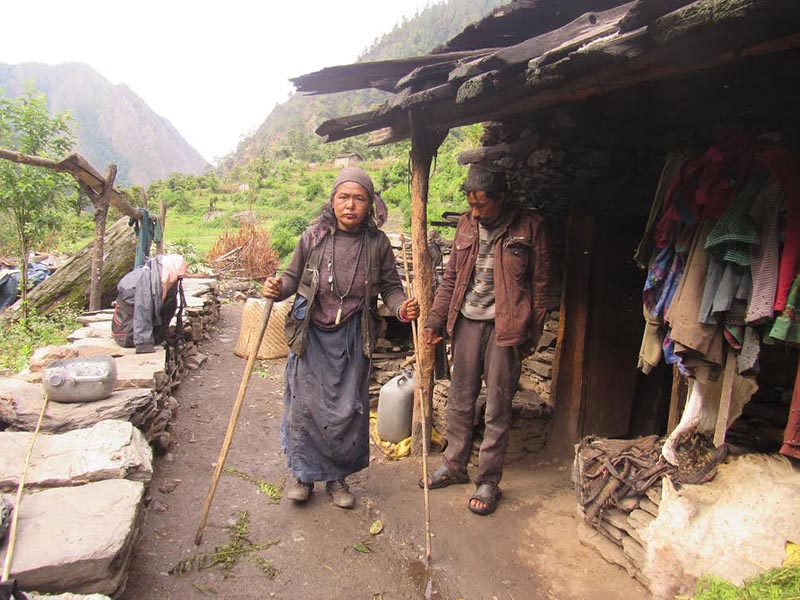 A woman with physical disability walking with the help of walking sticks  at Gumba village of Himali Rural Municipality, in Bajura, on Sunday, December 31, 2017. Photo: THT