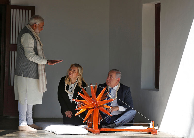Indian Prime Minister Narendra Modi explains to Israeli Prime Minister Benjamin Netanyahu how to spin cotton on a wheel watched by Netanyahu's wife Sara during their visit to Gandhi Ashram in Ahmedabad, India, on  January 17, 2018. Photo: Reuters