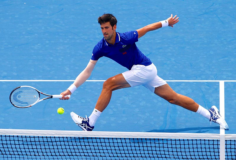Serbia's Novak Djokovic stretches for a shot during his match against Austria's Dominic Thiem during the Kooyong Classic exhibition tournament, at Kooyong Lawn Tennis Club, in Melbourne, Australia, on January 10, 2018. Photo: Reuters