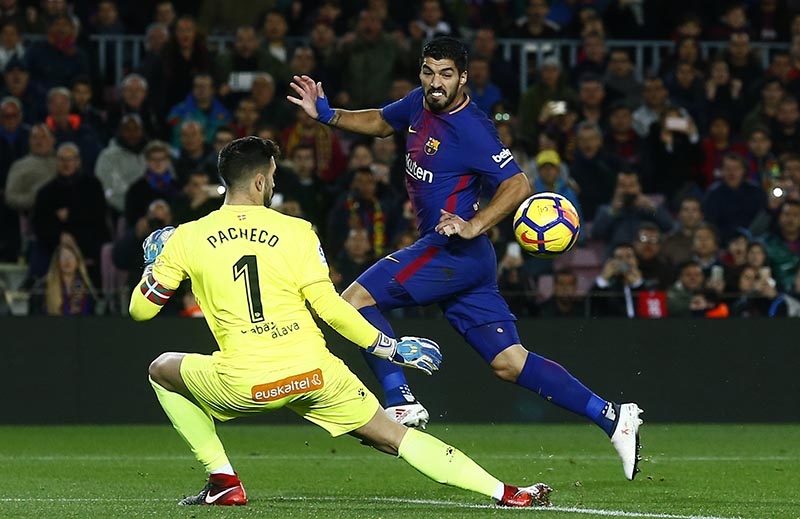 FC Barcelona's Luis Suarez (right), duels for the ball against Alaves'goalkeeper Fernando Pacheco during the Spanish La Liga soccer match between FC Barcelona and Alaves at the Camp Nou stadium in Barcelona, Spain, on Sunday, January 28, 2018. Photo: AP