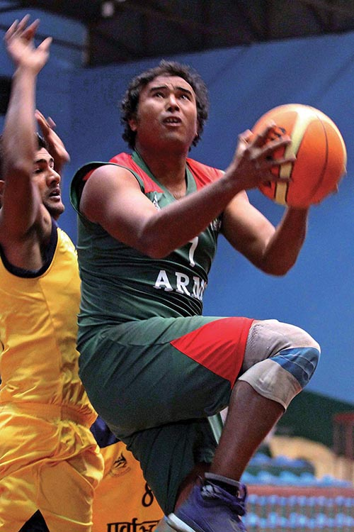 TAC's Binod Maharjan jumps for a basket under pressure from an Eastern Region opponent (left)  during the National Basketball Championship at National Sports Council covered hall, Tripureshwor in Kathmandu on Monday. Photo:  Udipt Singh Chhetry/ THT