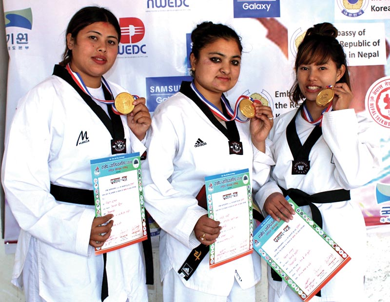 (From Left) Tawekwondo players Nisa Rawal, Apsara Karki and Sita Tamang hold their gold medals on the first day of the 14th National Taekondo Tournament in Lalitpur, on Thursday. Photo: THT
