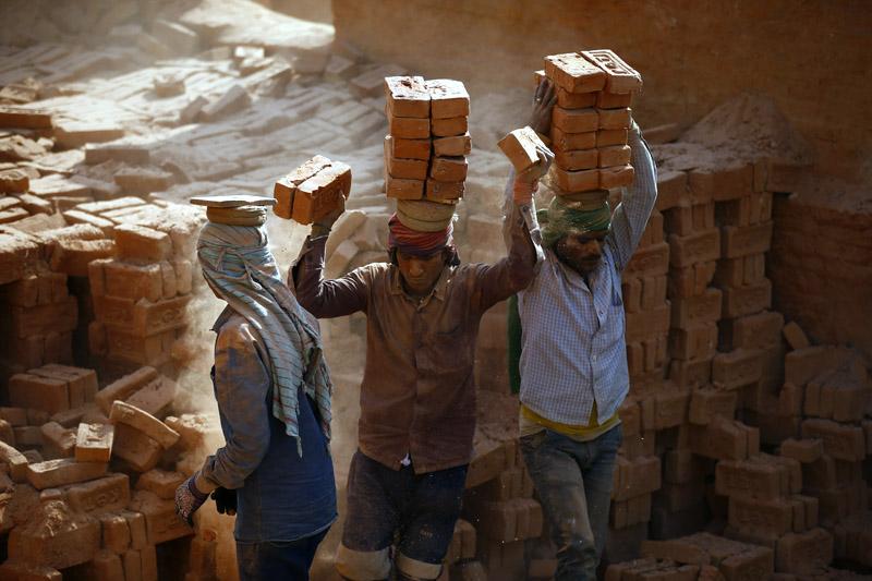 Migrant labourers balance bricks on their heads at a brick kiln in Bhaktapur, on Thursday, January 11, 2018. Photo: Skanda Gautam