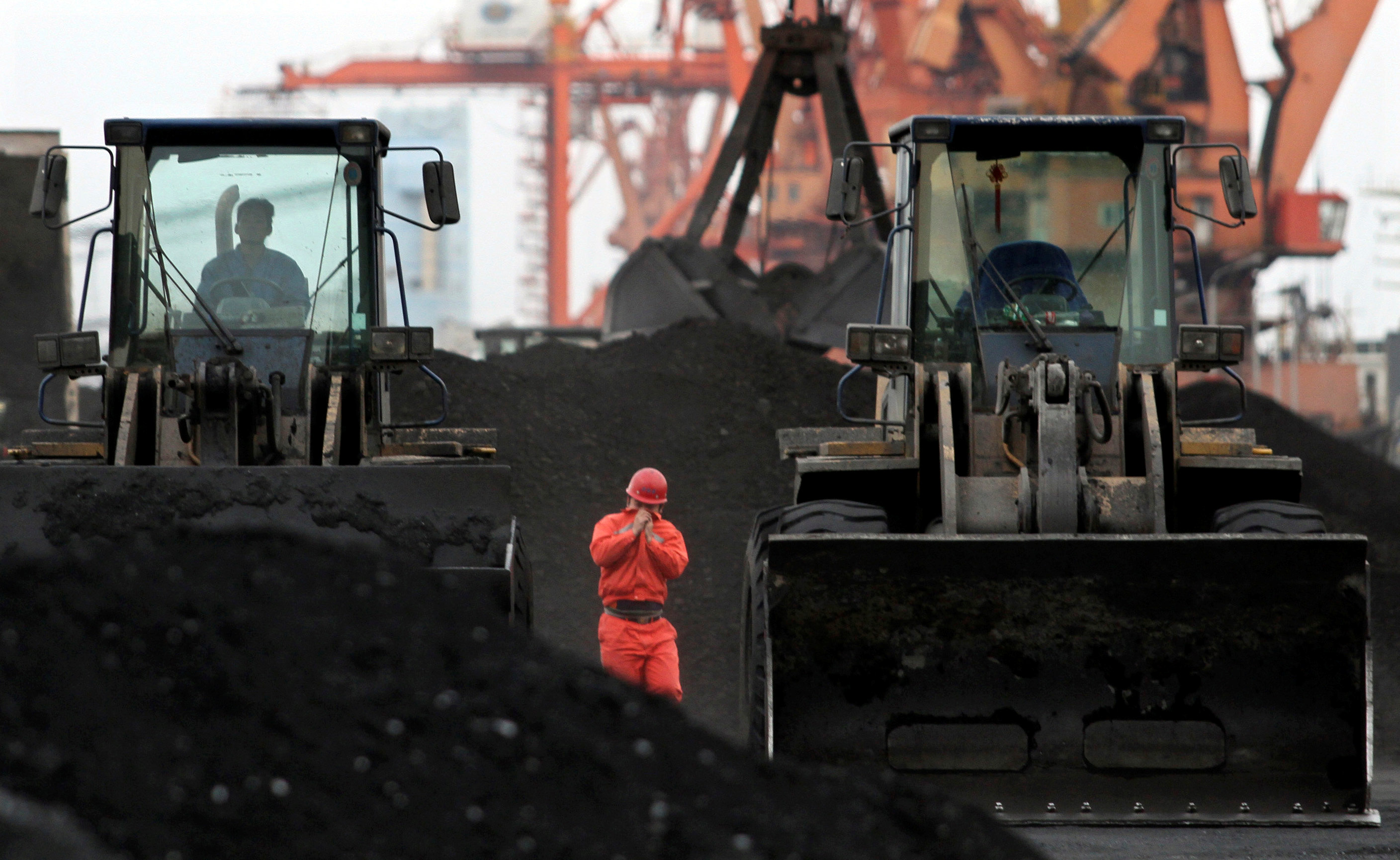 An employee walks between front-end loaders which are used to move coal imported from North Korea at Dandong port in the Chinese border city of Dandong, Liaoning province December 7, 2010. REUTERS/Stringer/File Photo   CHINA OUT. NO COMMERCIAL OR EDITORIAL SALES IN CHINA