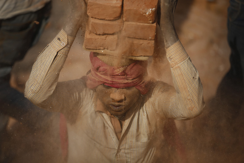 A migrant labourer balances stacked bricks on his head at a brick kiln in Bhaktapur, on Thursday, January 11, 2018. Photo: Skanda Gautam