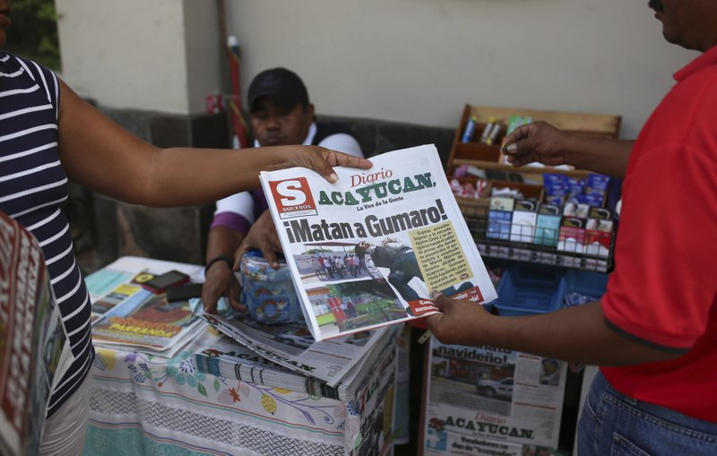 A man buys a newspaper carrying the Spanish headline u201cThey killed Gumaro!u201d on the sidewalk in Acayucan, Veracruz state, Mexico. For some, Gumaro Perez was an experienced reporter who earned the nickname u201cthe red manu201d for his coverage of bloody crimes in Acayucan, Veracruz, but in the eyes of prosecutors he was an alleged drug cartel operative who met a grisly end when he was shot dead on December 19, 2017. Photo: AP