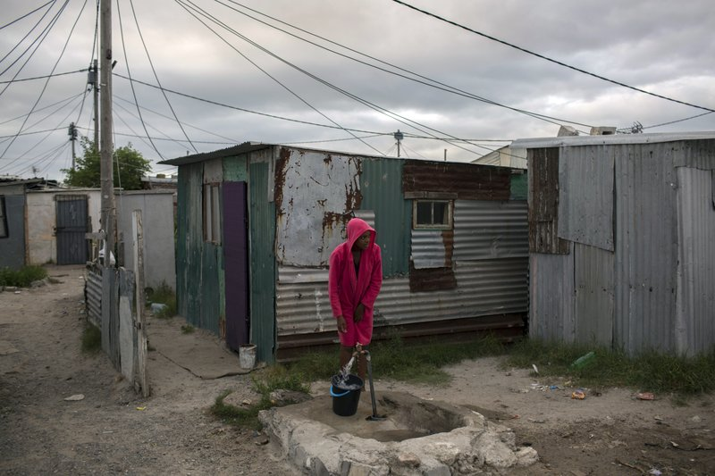 A woman collects water in a settlement near Cape Town on Friday, Feb. 2, 2018. South Africau2019s drought-hit city of Cape Town introduced new water restrictions in an attempt to avoid what it calls u201cDay Zero,u201d the day in mid-April when it might have to turn off most taps. (AP Photo/