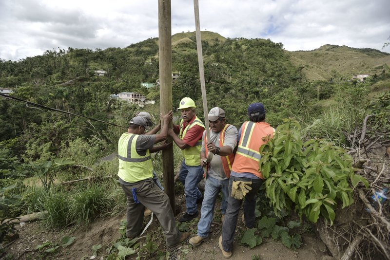 Jan 31, 2018 photo, Public Works Sub-Director Ramon Mendez, wearing hard hat, directs locals who are municipal workers, Eliezer Nazario, holding rope, Tomas Martinez, right, and Angel Diaz, left, as they install a power pole in an effort to return electricity to Felipe Rodriguezu2019s home, four months after Hurricane Maria in Coamo, Puerto Rico. As the number of mayors complaining about the slow power restoration has grown, the territoryu2019s administration allowed municipalities to sign an agreement with the islandu2019s power company to take over power restoration efforts if interested and relieve the agency of any responsibility. Photo: AP