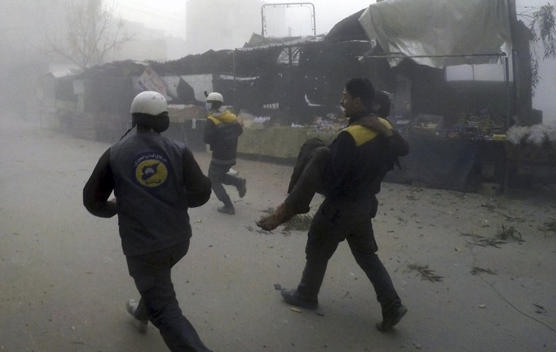 provided by the Syrian Civil Defense group known as the White Helmets, shows a civil defense worker carrying a wounded man after airstrikes hit a rebel-held suburb near Damascus, Syria, Monday, Feb. 5, 2018. The Syrian Observatory for Human Rights says waves of airstrikes hit at least five neighborhoods in the Eastern Ghouta suburb, the only remaining rebel stronghold near the capital, Damascus. Photo: AP