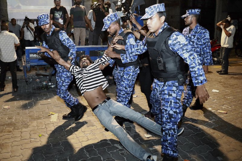 Feb. 2, 2018, file photo, Maldivian police officers detain an opposition protestor demanding the release of political prisoners during a protest in Male, Maldives. As a political crisis plays out in the Maldives, a quiet tug of war is taking place around it, with regional heavyweights China and India vying for strategic dominance in the picturesque Indian Ocean nation.