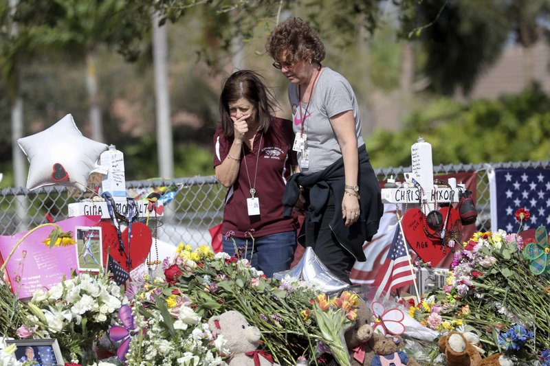 Margarita Lasalle, a bookkeeper and Joellen Berman, a guidance data specialist, look at a memorial Friday, Feb. 23, 2018 as teachers and school administrators returned to Marjory Stoneman Douglas High School for the first time since 17 victims were killed in a mass shooting at the school, in Parkland. Photo: AP
