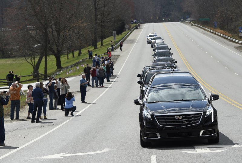 People line the street as the hearse carrying the body of Rev. Billy Graham leaves the Billy Graham Training Center at the Cove on Saturday, Feb. 24, 2018 in Asheville, N.C. Grahamu2019s body will be brought to his hometown of Charlotte on Saturday as part of a procession expected to draw crowds of well-wishers. Photo: AP