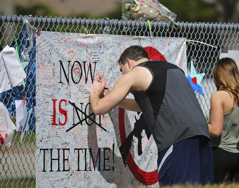 A man signs a banner as people pay tribute at a memorial for the victims of the shooting at Marjory Stoneman Douglas High School on Sunday, February 25, 2018. photo: AP
