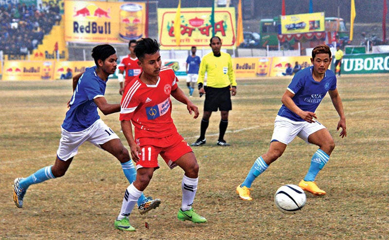 Nepal Police Clubu2019s RejinSubba (centre) vies for the ball with Kakarvitta Football Training Centre players during their 20th BudhaSubba Gold Cup match at the Dharan Stadium in Dharan on Monday. Photo: THT