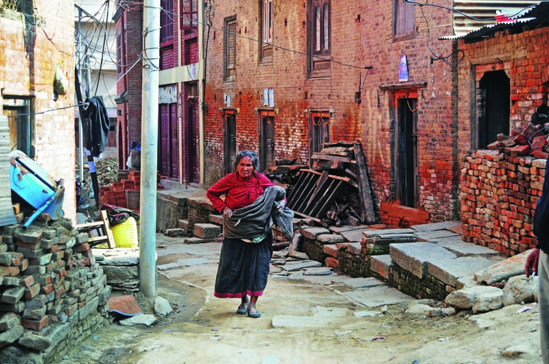 An elderly woman walking through an alley in Khokana, on the outskirts of Lalitpur, on Wednesday. Photo: THT Print