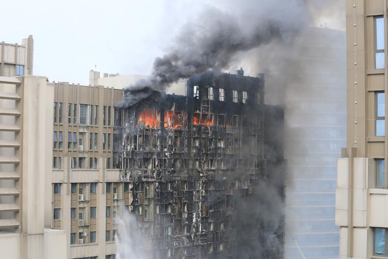 Smoke and flames are seen engulfing a 20-storey office building in Zhengzhou, Henan province, China February 1, 2018. Photo: Reuters/Stringer