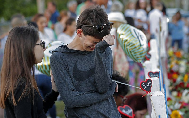 Daniel Bishop, 16, a student at Marjory Stoneman Douglas High School, cries at a makeshift memorial outside the school, in Parkland, Fla., on Sunday, Feb. 18, 2018. Photo: AP