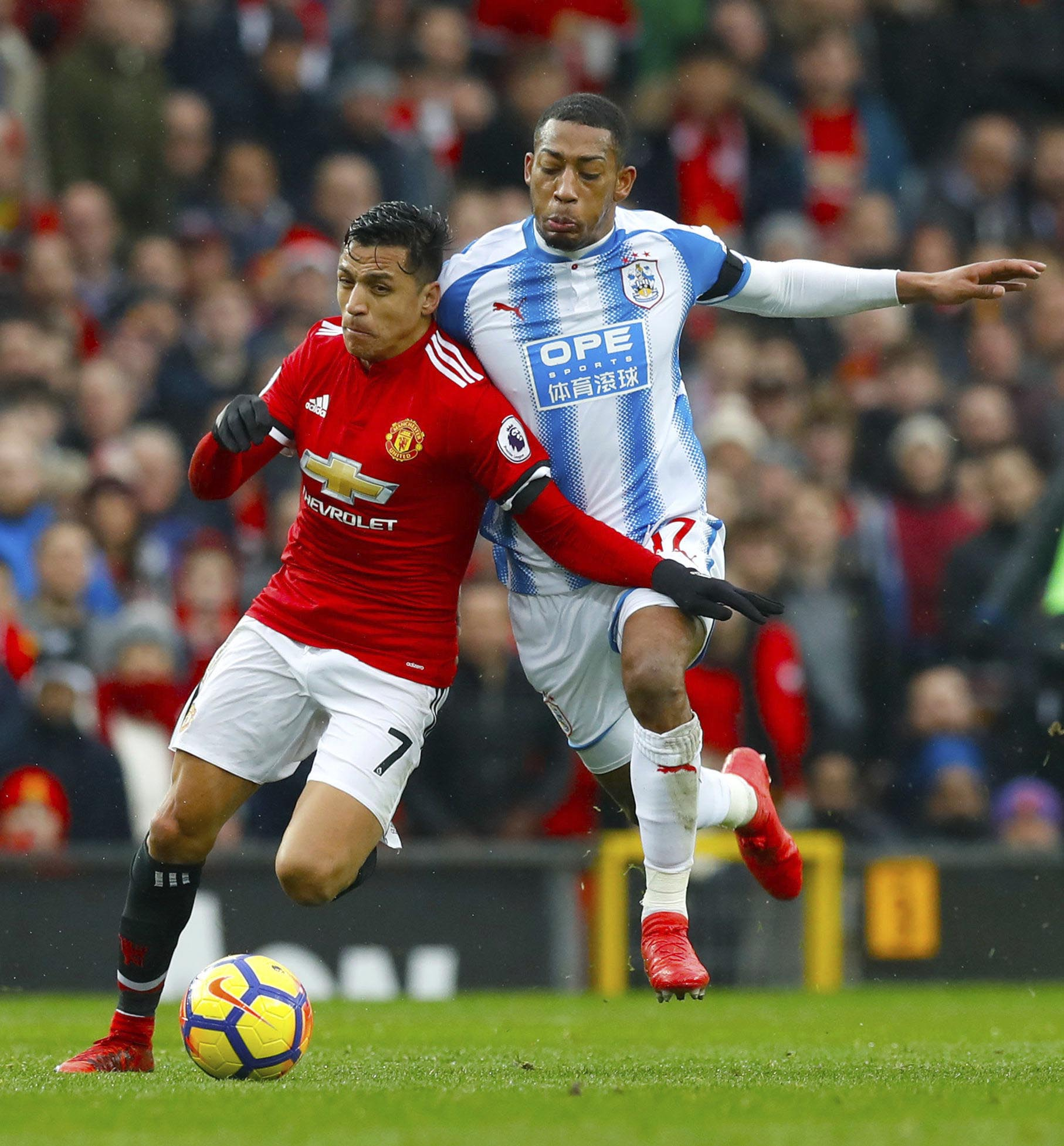 Manchester United's Alexis Sanchez (left), and Huddersfield Town's Rajiv van La Parra in action during their English Premier League soccer match at Old Trafford in Manchester, England, Saturday Feb. 3, 2018. (Martin Rickett/PA via AP)