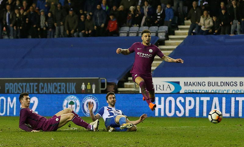 Wigan Athleticu2019s Will Grigg scores their first goal as Manchester City's Kyle Walker and Aymeric Laporte look on during the FA Cup Fifth Round match between Wigan Athletic and Manchester City, at DW Stadium, in Wigan, Britain, on February 19, 2018. Photo: Reuters