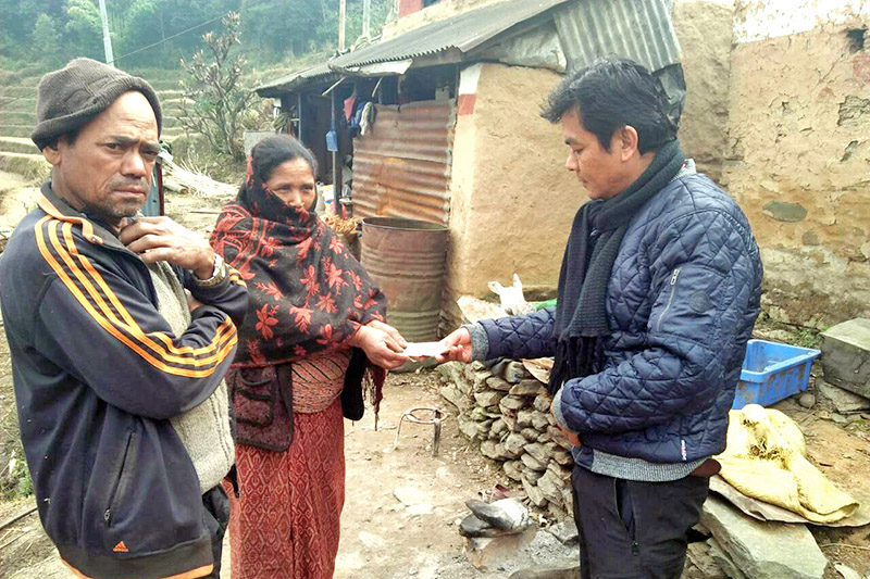 A man hands over a cheque to the mother, whose two children are suffering from congetinal disorder, at Dehi village in Pokhara Lekhnath Metropolitan City-13, on Saturday, February 03, 2018. People from all walks of life have started to extend their support to the family after a  related news was covered in THT Online. Photo: Bharat Koirala