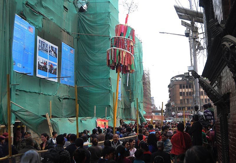 People gather to watch Chir, a bamboo pole fringed with colourful strips of cloth, being installed to mark the beginning of Holi festival, in Kathmandu, on Friday, February 23, 2018. Photo: Balkrishna Thapa Chhetri