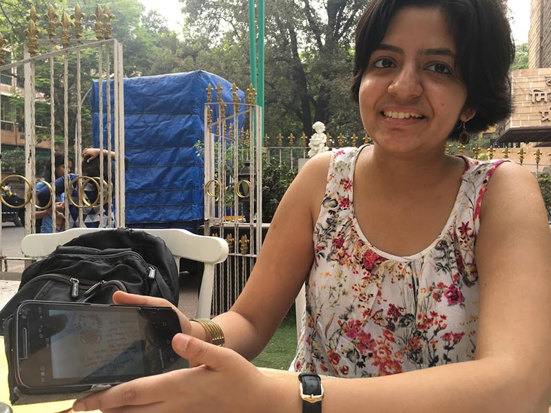 Tuberculosis (TB) survivor Nandita Venkatesan, who helps TB patients tackle stigma, scrolls through messages she receives from them on her mobile phone in Mumbai, on February 6, 2018. Photo: Thomson Reuters Foundation