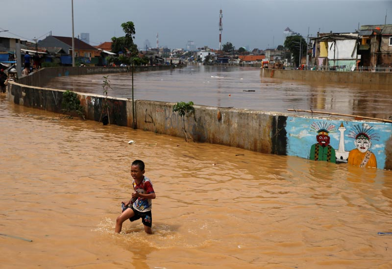 A child wades through a flooded street in Jatinegara district in Jakarta, Indonesia February 6, 2018. REUTERS/Beawiharta
