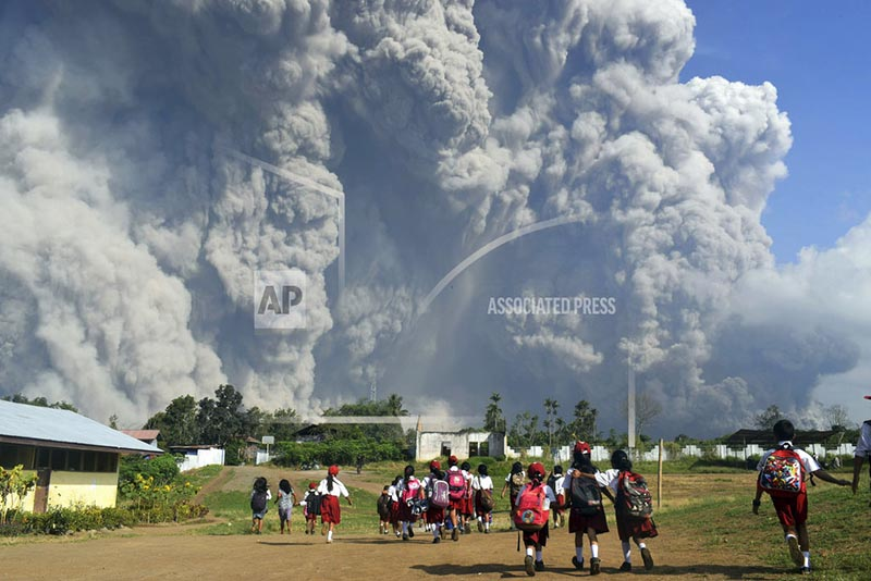 School children walk as Mount Sinabung erupts in Karo, North Sumatra, Indonesia, Monday, February 19, 2018. Photo: AP