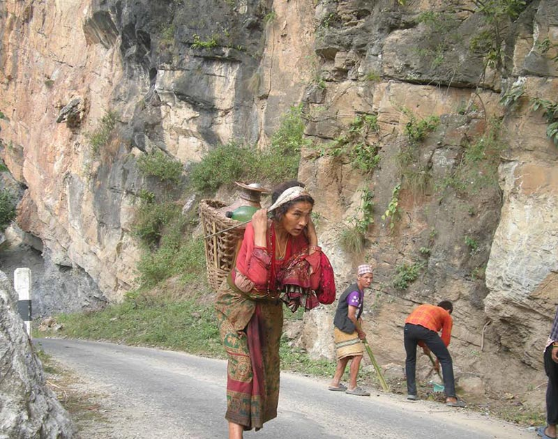 A woman returning home after fetching drinking water from the Bhutiya River, in Khotang, on Saturday. Photo: THT
