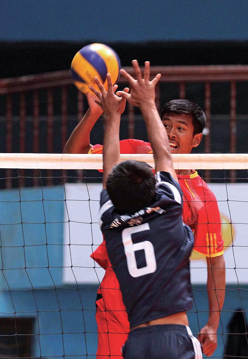 Raju Sherchan of NPC attempts a spike against Nayabazar Samajik Club during their NST-NVA Club Volleyball Championship match at the NSC covered hall in Kathmandu on Monday. Photo: THT