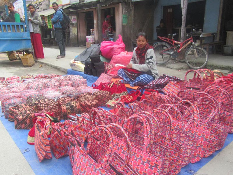 A street vendor woman waits for customers beside caps and Ladiesu0092 handbags kept for sale at Tarhara in Itahari of Sunsari district, on Friday, February 9, 2018. Photo: RSS
