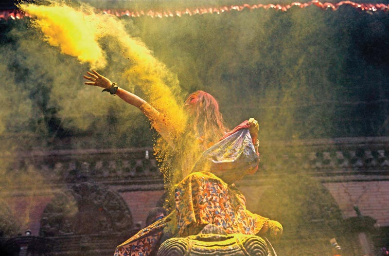 A woman hurls colored vermillion powder during celebrations of Holi festival, also known as the festival of colors in Basantapur Durbar Square, a UNESCO world heritage site in Kathmandu, Nepal on Tuesday, March 22, 16.
