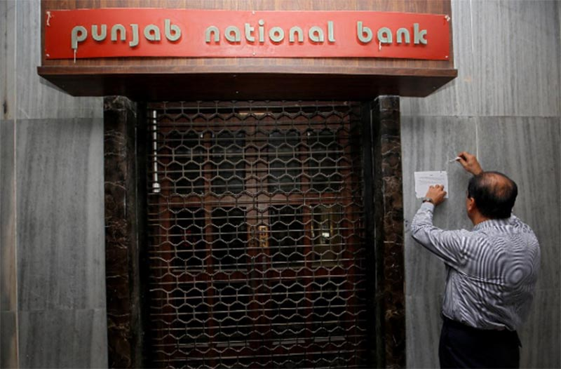 A man tries to remove a notice pasted on the wall of a Punjab National Bank branch after it was sealed by India's federal police in Mumbai, India, on February 19, 2018. Photo: Reuters