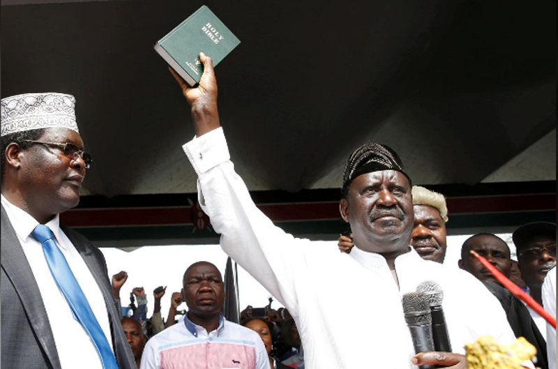 FILE- Kenyan opposition leader Raila Odinga of the National Super Alliance (NASA) holds a bible as he takes a symbolic presidential oath of office in Nairobi, Kenya January 30, 2018. Photo: Reuters