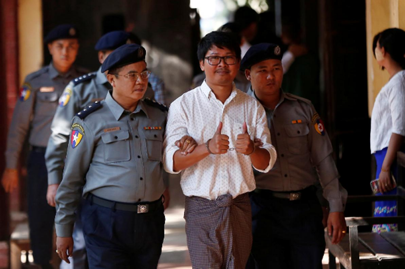 FILE: Detained Reuters journalist Wa Lone escorted by police, arrives for a court hearing in Yangon, Myanmar February 6, 2018. Photo: Reuters.