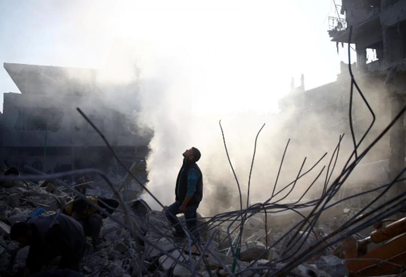 A man stands on rubble of damaged buildings after an airstrike in the besieged town of Hamoria, Eastern Ghouta, in Damascus, Syria Janauary 9, 2018. Photo: Reuters