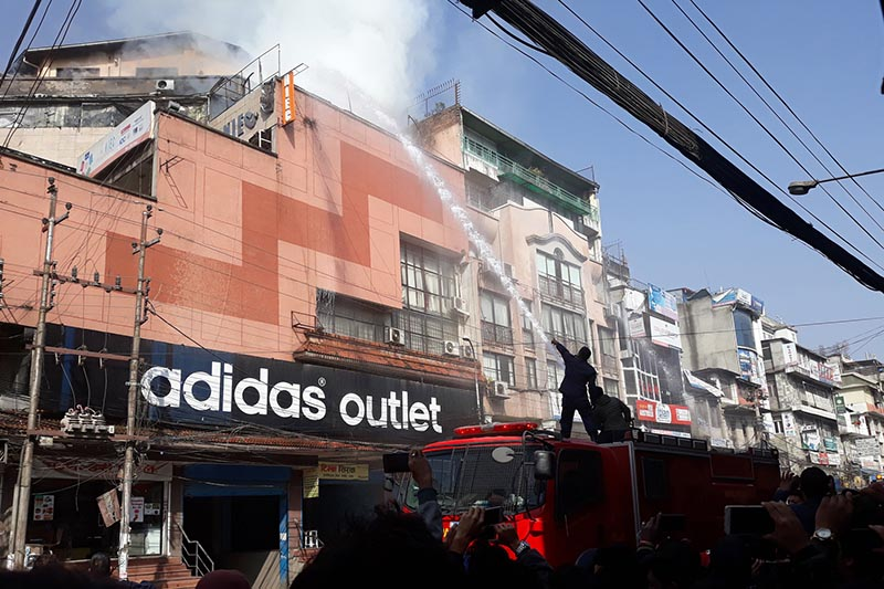Fire fighters water the Share Market building to douse the fire that erupted in Putalisadak, Kathmandu, on Monday, February 26, 2018. Photo: RSS