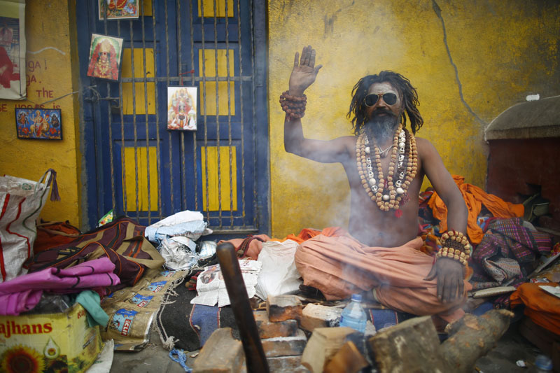 A Sadhu poses as he keeps himself warm with firewood on the eve of the Mahashivaratri festival inside Pashupatinath Temple in Kathmandu, on Monday, February 12, 2018. Thousands of sadhus from Nepal and India celebrate the festival by smoking marijuana, smearing their bodies with ash and offering prayers devoted to the Hindu Deity Lord Shiva. Photo: Skanda Gautam