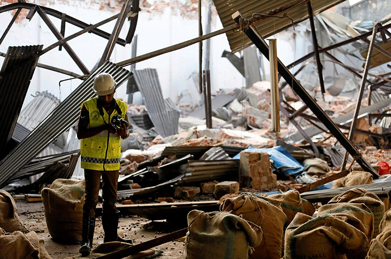 A police officer inspects the collapsed old tea warehouse in Colombo, Sri Lanka, on February 14, 2018. Photo: Reuters