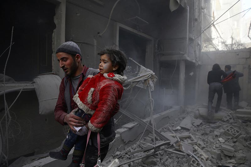 A man holds a child after an airstrike in the besieged town of Douma, Eastern Ghouta, Damascus, Syria, on  February 7, 2018. Photo: Reuters