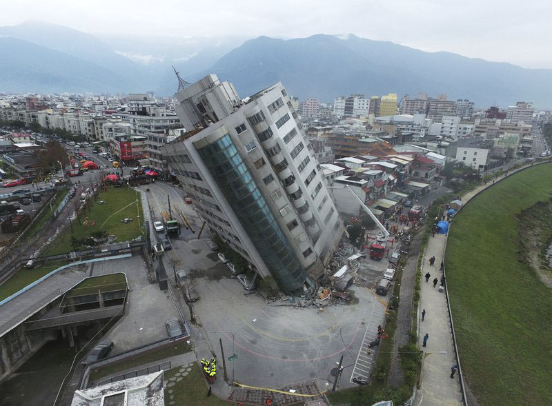 FILE - In this February 7, 2018, file photo, a residential building leans on a collapsed first floor following an earthquake, in Hualien, southern Taiwan. A memorial service is being held on Monday, February 12, 2018, for the 17 people who died after the strong earthquake hit Taiwanu0092s east coast last week. Members of the military and police force, religious group volunteers and city workers paid their respects before a row of the victimsu0092 framed photographs. Photo: AP