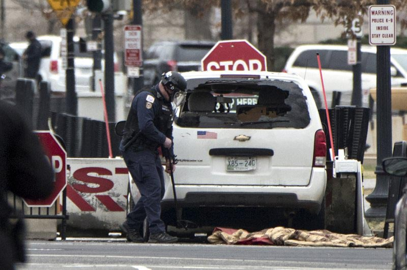 A Secret Service officer checks a white passenger vehicle that struck a security barrier that guards the southwest entrance to the White House grounds off of 17th Street n Washington, on Friday, Feb. 23, 2018. Photo: AP