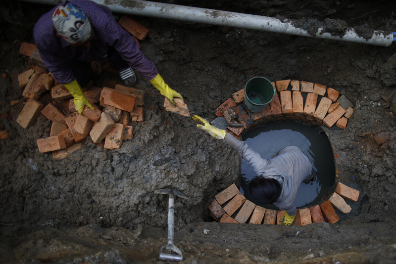 Workers pass bricks as they install sewage and water pipes on the main road at Baneshwor in Kathmandu, on Thursday, February 22, 2018. The delay in completion of road repair and construction has created a lot of hassles for the residents in these areas. Photo: Skanda Gautam