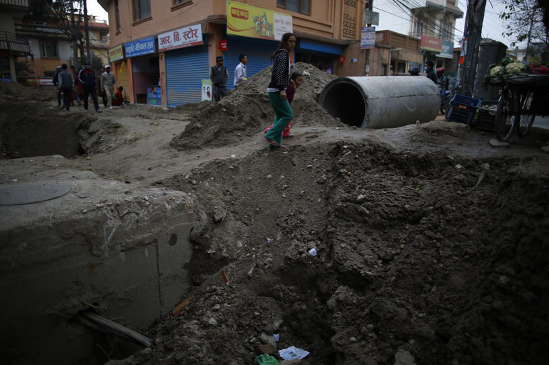 Pedestrians walk along a hole on a main road due to the ongoing sewage and water pipes installation at Baneshwor in Kathmandu,on Thursday, February 22, 2018.