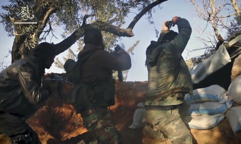 File - This frame grab from video provided , by the Syrian insurgent group Failaq al-Rahman, shows fighters with Failaq al-Rahman firing their weapons during clashes with government forces in the suburbs of the Syrian capital Damascus on Nov. 24, 2017. Photo: AP