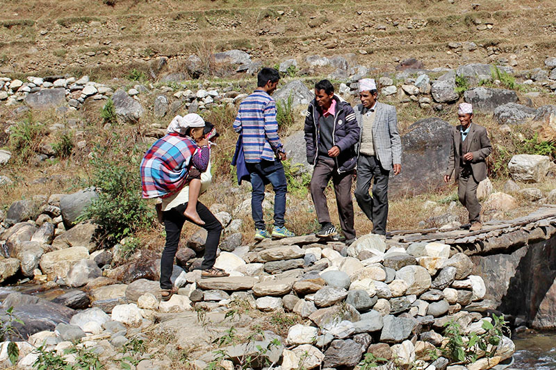 A man carries a sick woman on his back to a nearby health post in Jajarkot district, on Friday, February 23, 2018. Photo: RSS