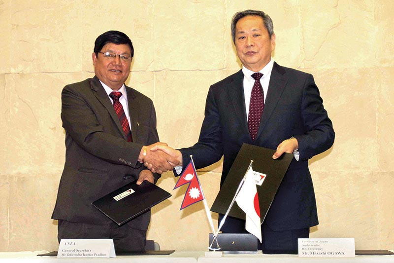 Japanese Ambassador to Nepal Masashi Ogawa and ANFA General Secretary DhirendraPradhan (left) exchanging the MoU at a programme in Kathmandu on Wednesday. Photo: THT
