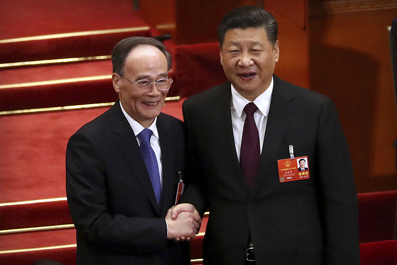 Chinese President Xi Jinping, right, shakes hands with Wang Qishan after Wang was elected Vice-President during a plenary session of China's National People's Congress (NPC) in Beijing, on Saturday, March 17, 2018. Photo: AP